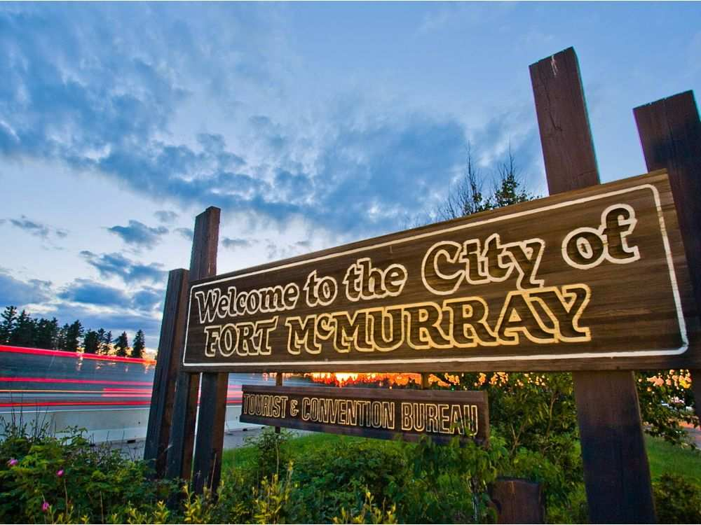 a-welcome-to-fort-mcmurray-sign-stands-on-the-side-of-highwa
