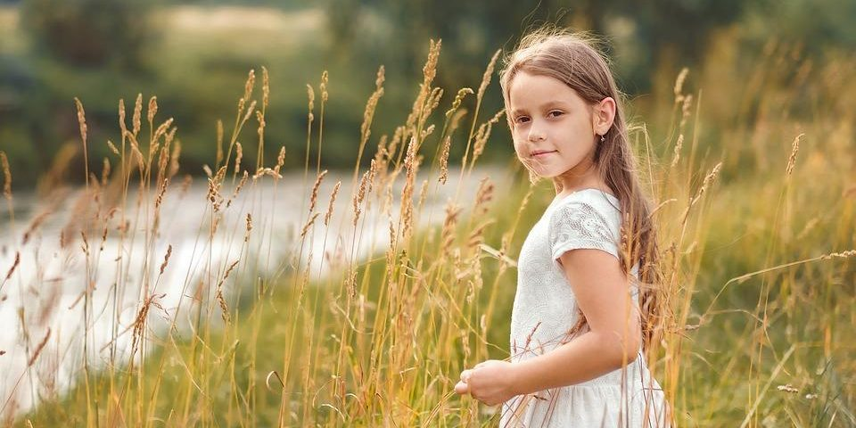 a young girl in a field of wheat