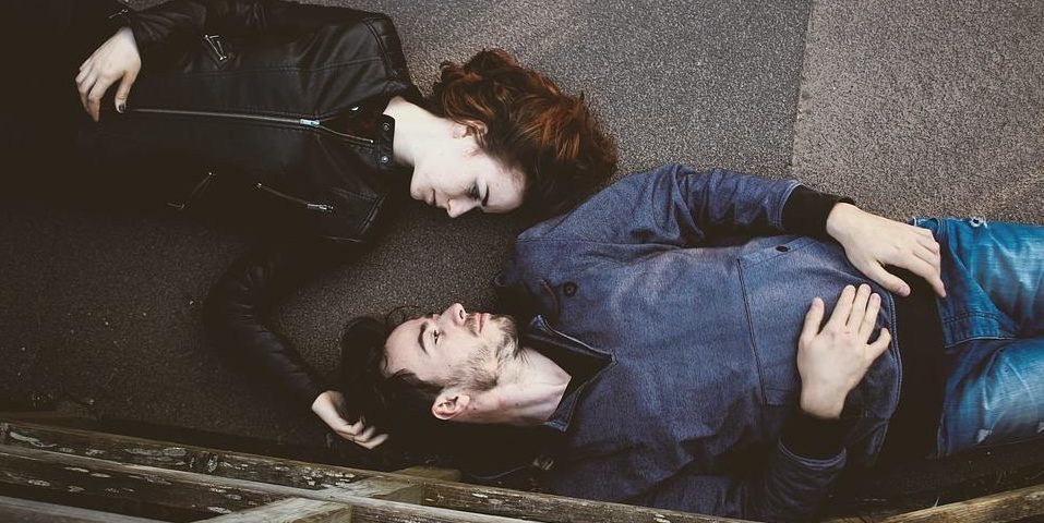 couple lying on the ground facing each other