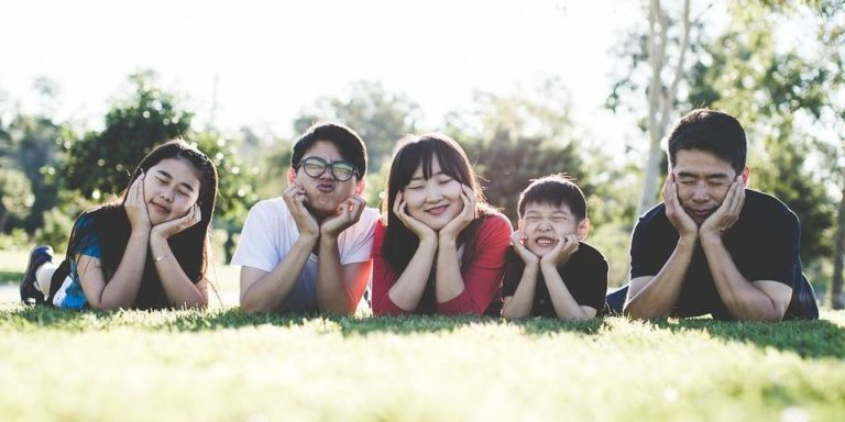 Asian family laying on the grass in Edmonton