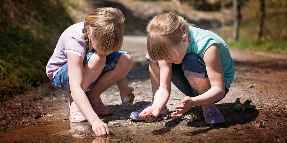 two young girls looking at a puddle