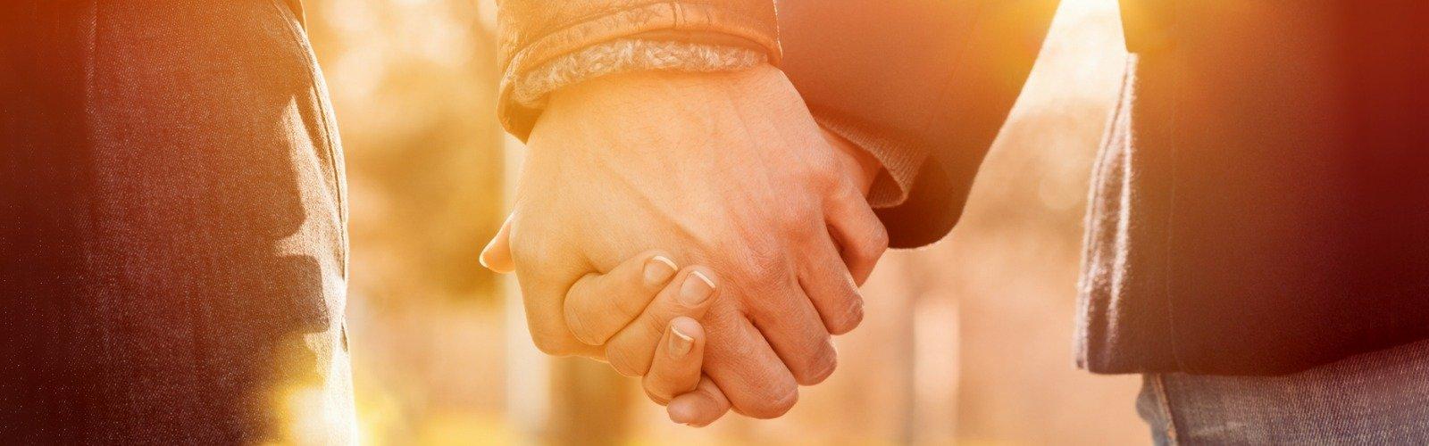 two hands holding sunset lighting