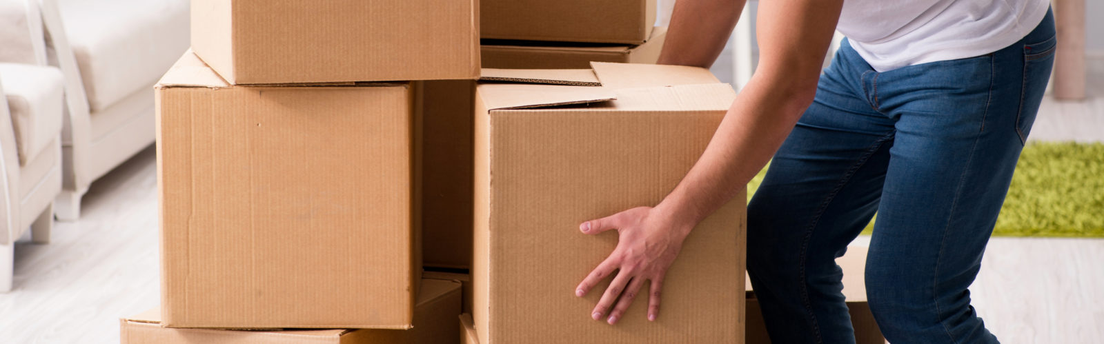 Young man moving boxes at psychological office
